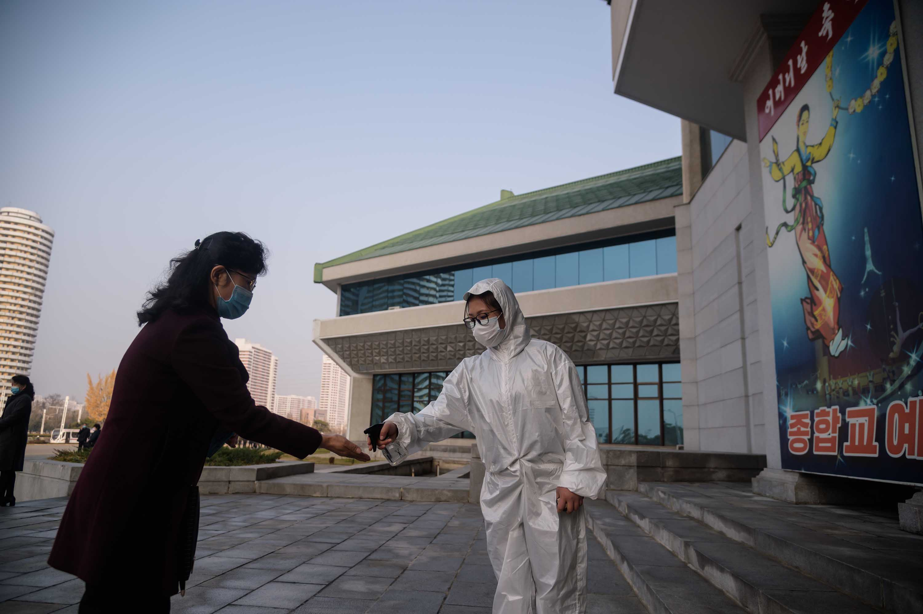 As part of preventative measures against coronavirus, a worker takes the temperature of an attendee ahead of a performance by North Korea's National Acrobatic Troupe in Pyongyang, North Korea, on November 16.