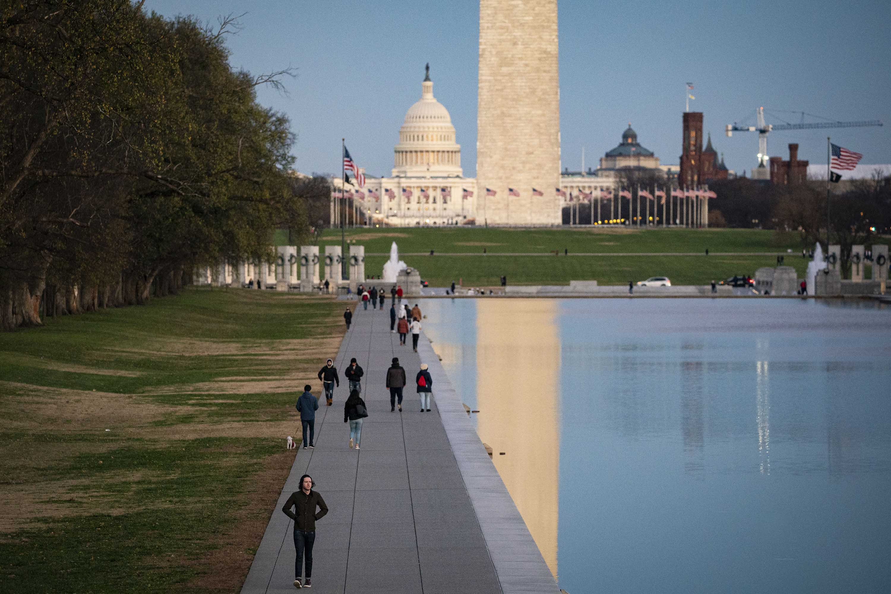 The U.S. Capitol and Washington Monument are pictured as people walk along the Reflecting Pool on the National Mall, on December 6, in Washington, DC.