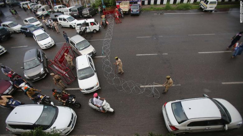 Indian police erect barbed wire across a road in Jammu on Monday.