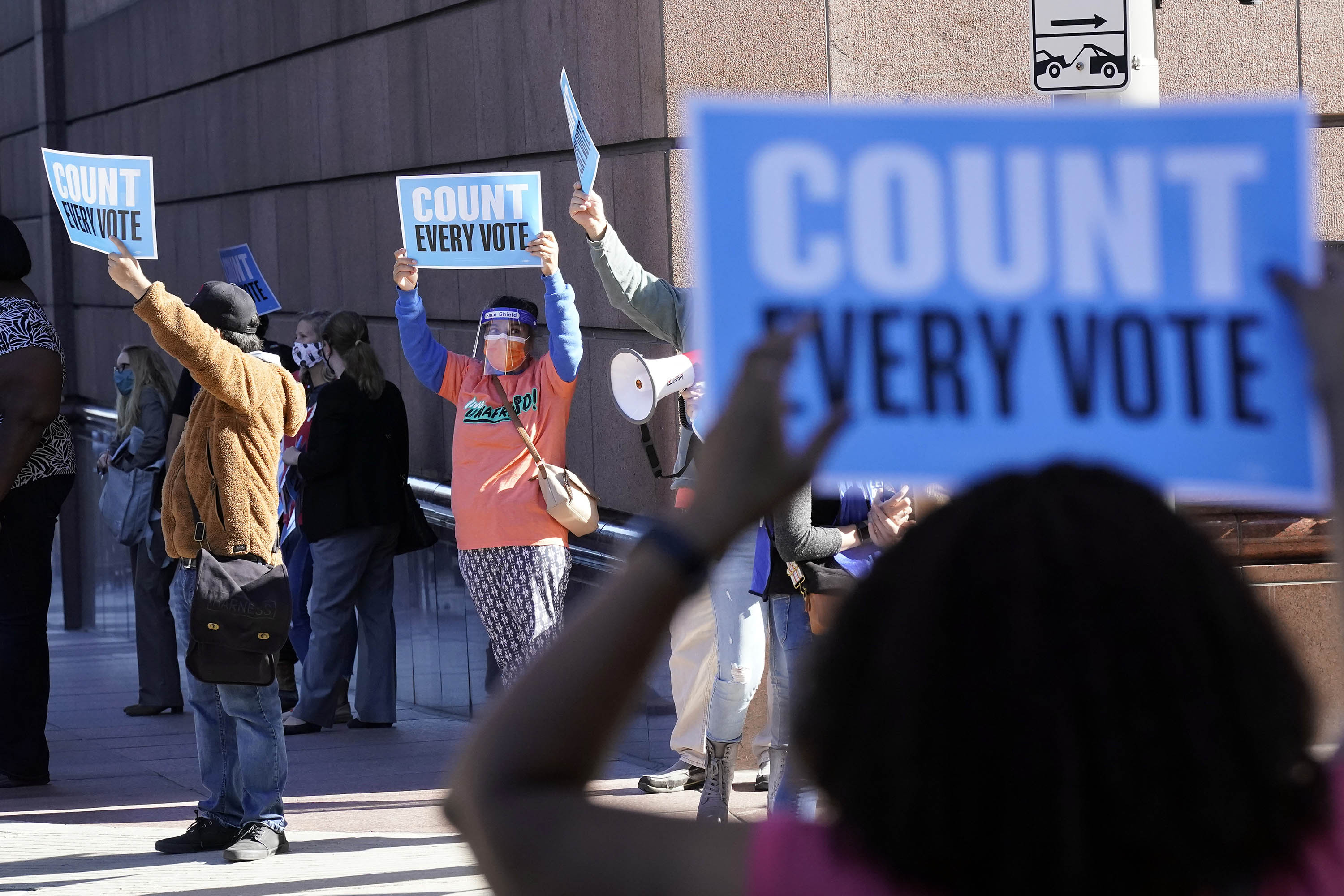 Demonstrators stand across the street from the federal courthouse in Houston, Texas, on Monday, before a hearing in federal court involving drive-thru ballots cast in Harris County.