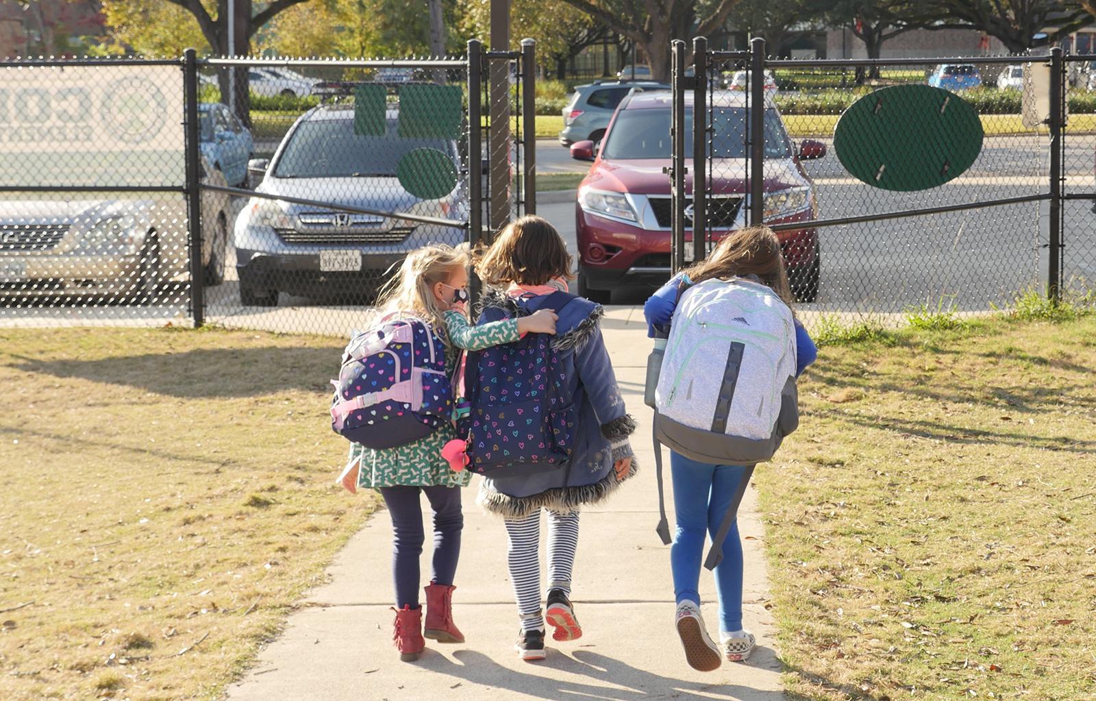 School children wearing facemasks walk outside Condit Elementary School in Bellaire, outside Houston, Texas, on December 16, 2020.