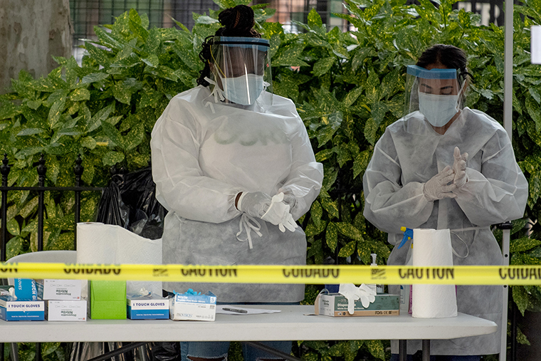 Two medical workers change their gloves at a free coronavirus testing location outside Washington Square Park on Monday, July 20.