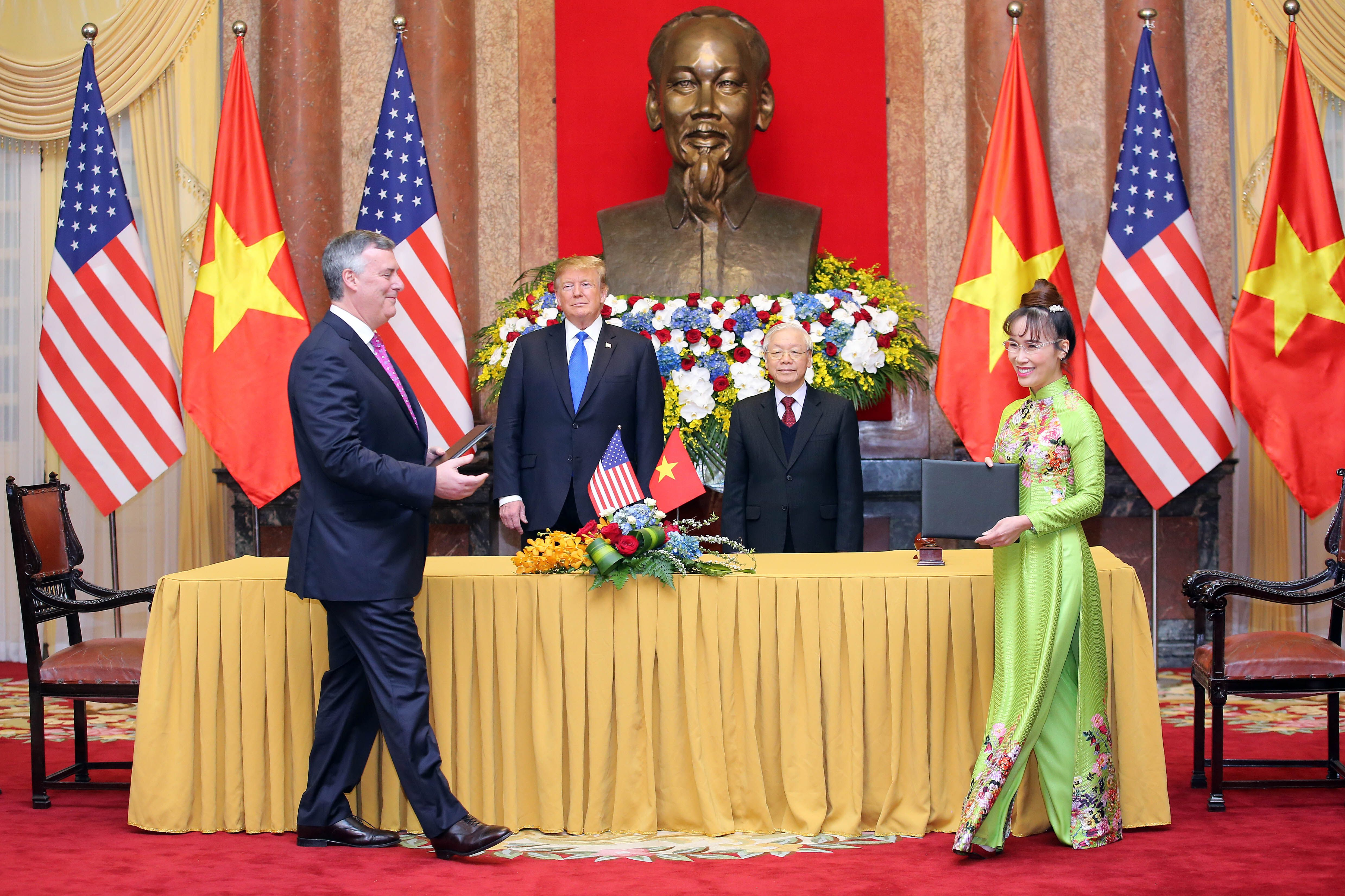 President Trump (center, left) and his Vietnamese counterpart Nguyen Phu Trong (center, right) witness a signing ceremony between President and CEO of VietJet aviation join stock company Nguyen Thi Phuong Thao (right) and President and CEO of Boeing Commercial Airplanes Kevin McAllister (left) in February