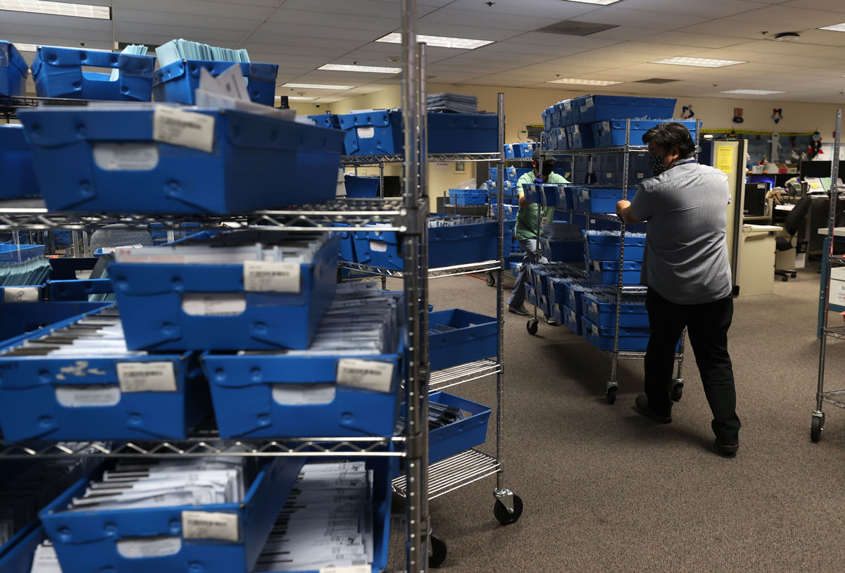 George Hiu and Alfred Gonzales move a cart stacked with trays of mail-in ballots at the Santa Clara County registrar of voters office on October 13 in San Jose, California.