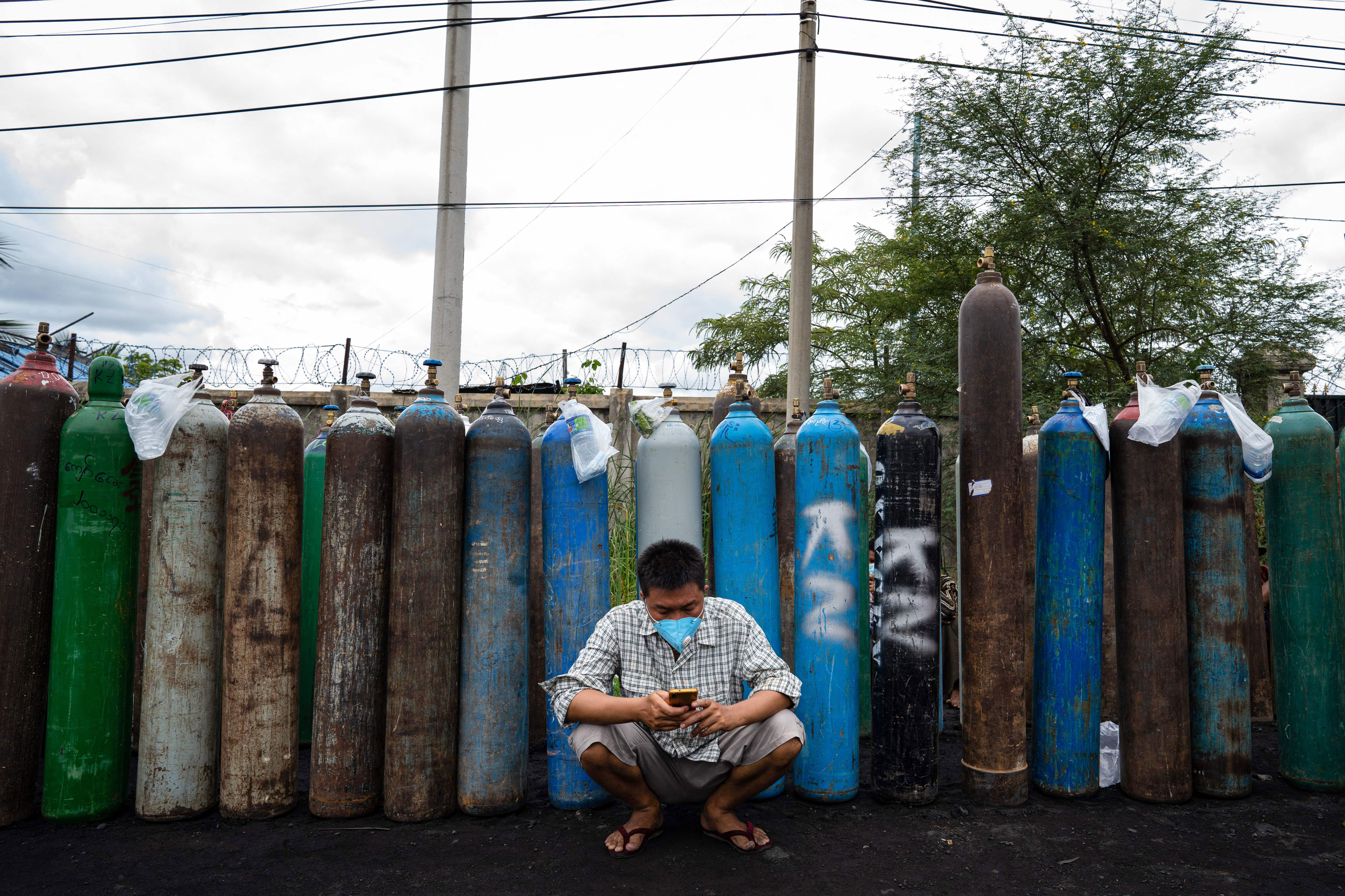 A person sits by empty oxygen canisters, which people are waiting to fill up, outside a factory in Mandalay, Myanmar, on July 13, 2021.