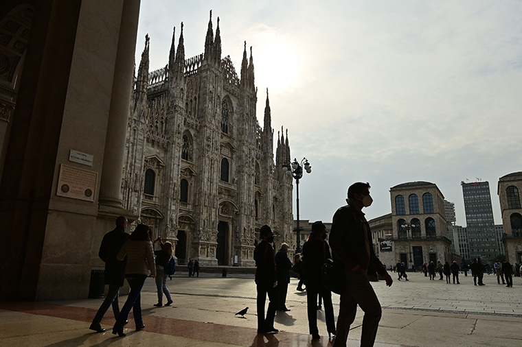 Milan on October 20, 2020 in front of the Duomo shows people walking across and wearing protective face masks.