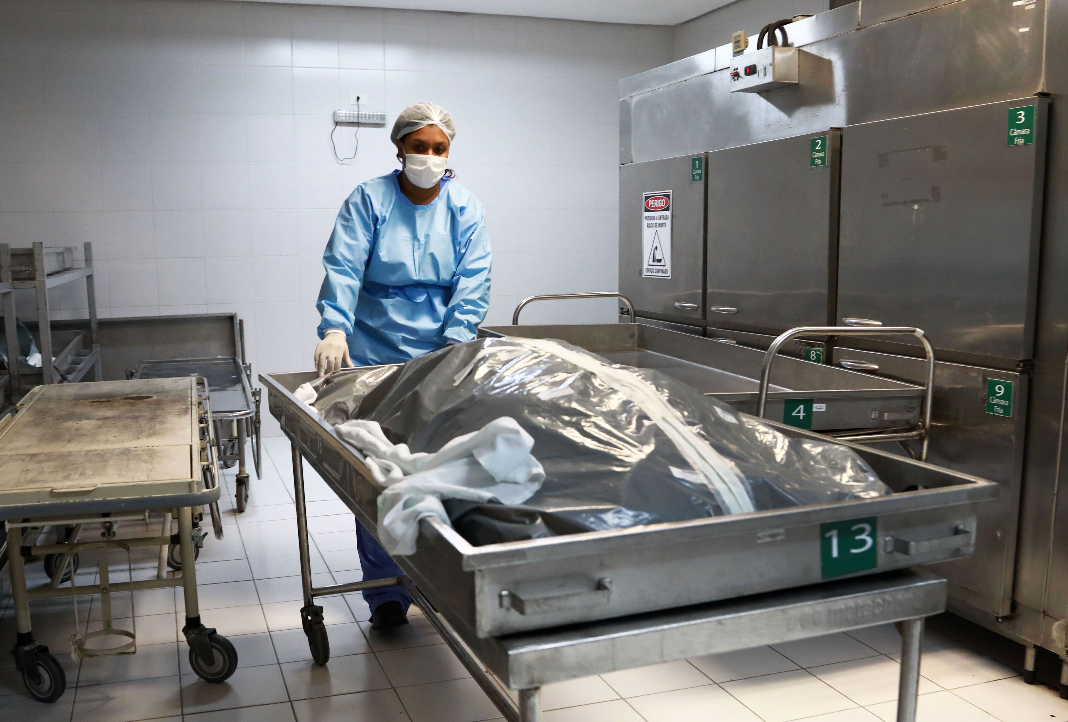 A morgue employee works with the body of a Covid-19 victim at a hospital in Porto Alegre, Brazil, on March 4.