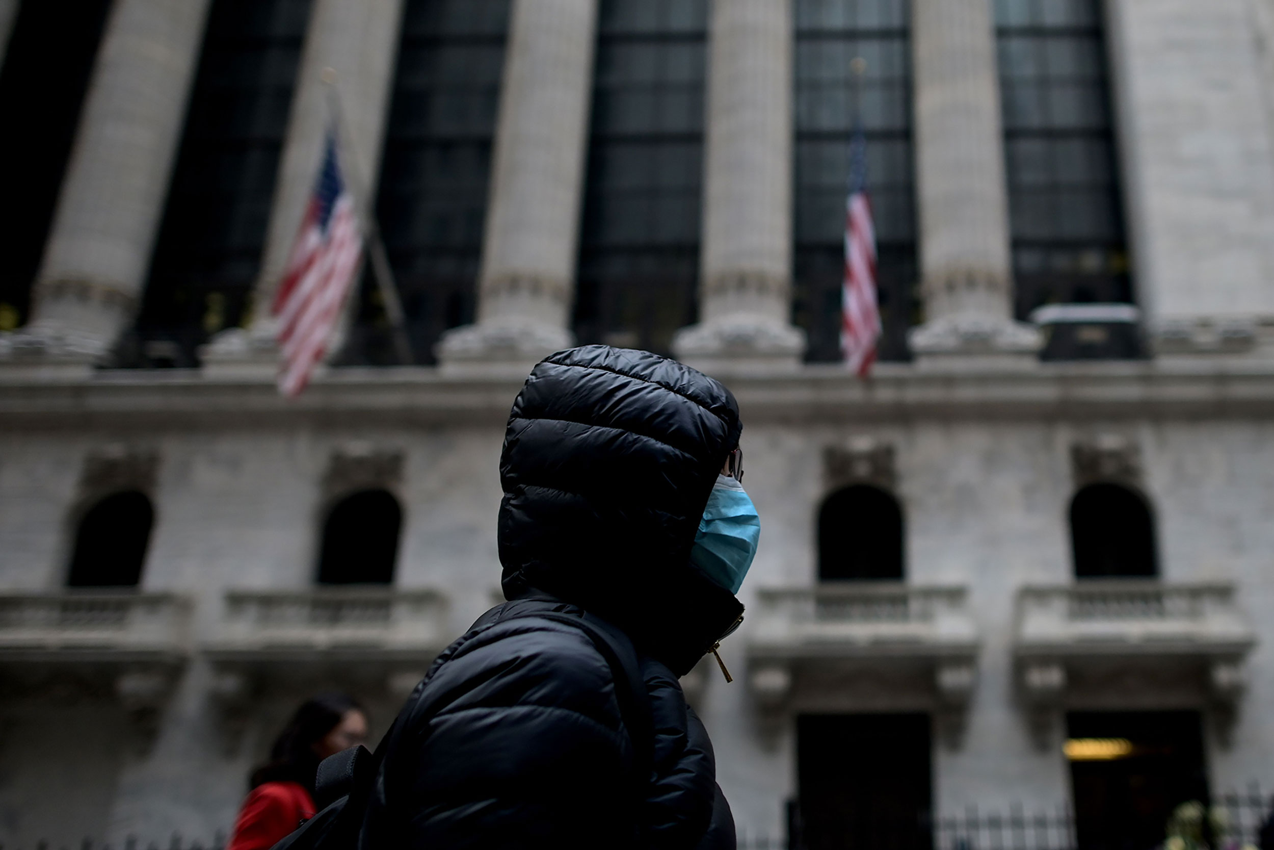 A person wearing a surgical mask walks past the New York Stock Exchange on February 3.