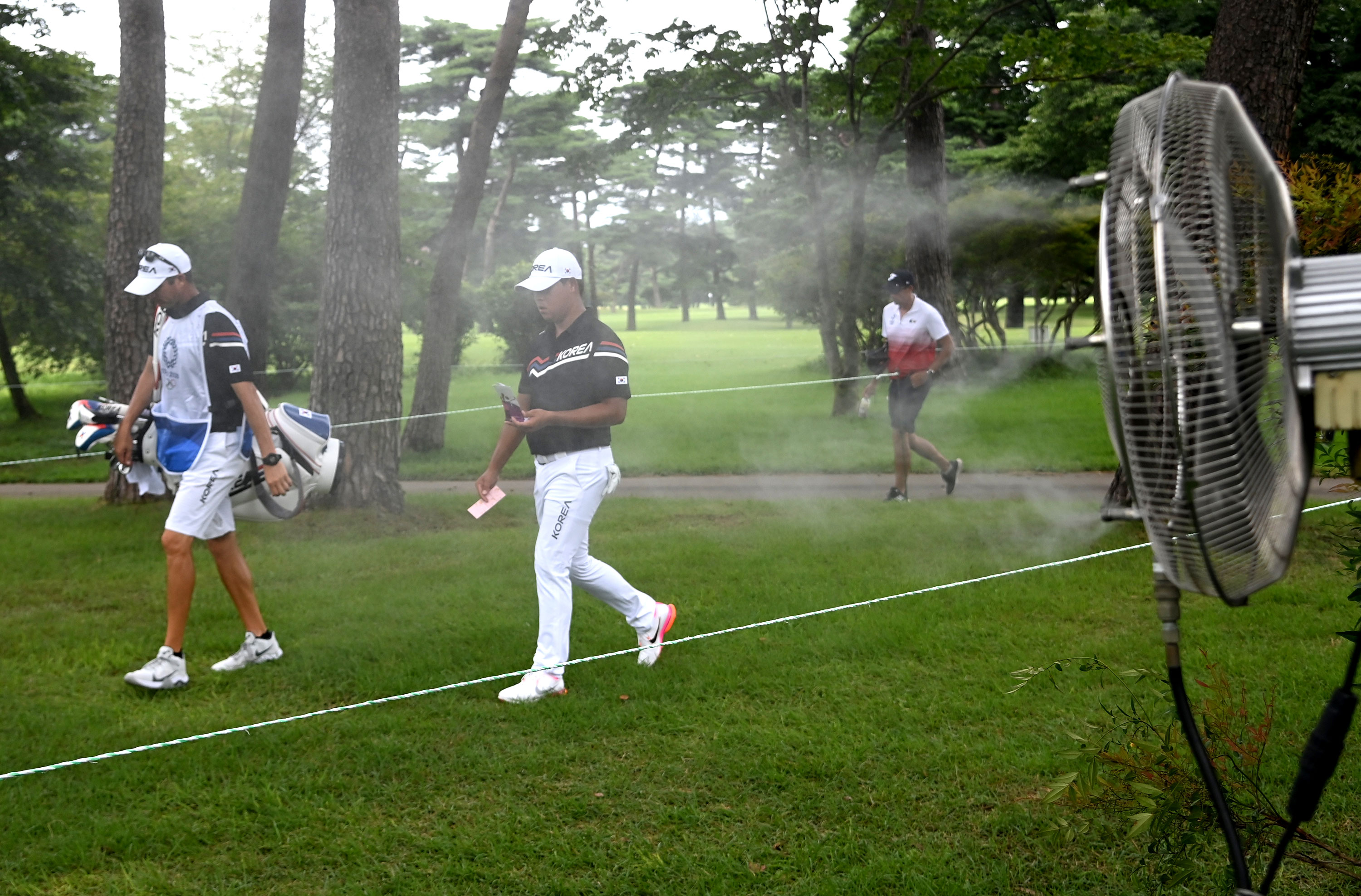 Kim Si Woo of South Korea walks past a fan spraying mist during golf competition in Kawagoe, Japan, on July 29.