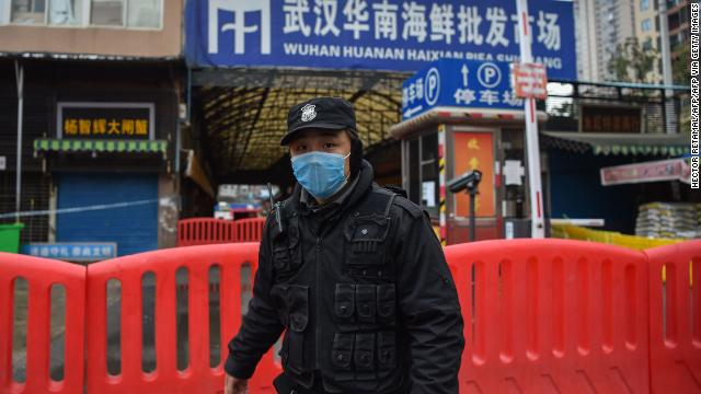 A police officer stands guard outside of Huanan Seafood Wholesale market where the coronavirus was detected in Wuhan.