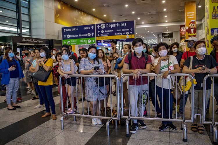 Greeters wearing face masks wait for arriving travelers at the arrival area of Ninoy Aquino International Airport on March 10, in Manila, Philippines.