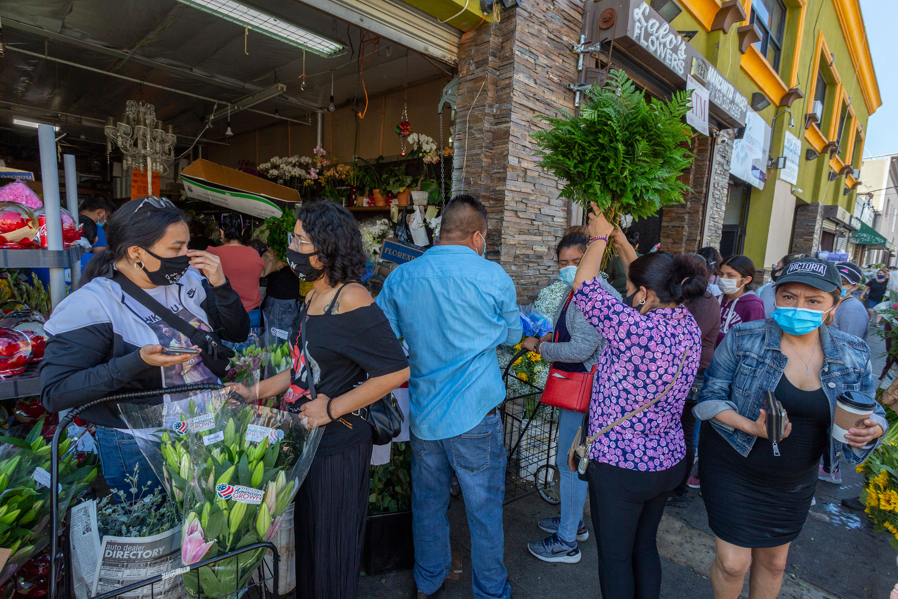 People mingle in close proximity to one another as businesses in the flower district reopen on May 8, in Los Angeles, California.