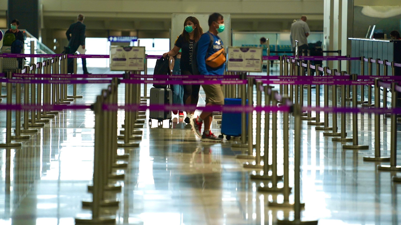 Passengers walk through the Hong Kong International Airport on March 10.