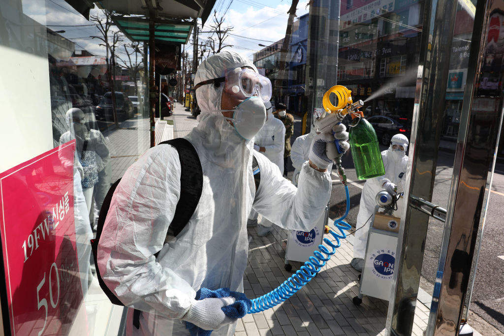 Cleaners wearing protective gear spray antiseptic solution against the coronavirus (COVID-19) on February 27, 2020 in Seoul.