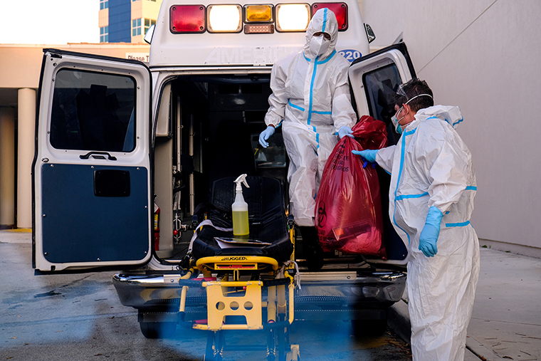 EMTs cleanse their materials outside Memorial West Hospital where coronavirus disease (COVID-19) patients are treated, in Pembroke Pines, Florida, on July 13.