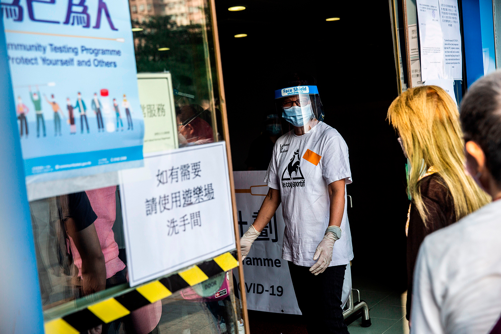 A staff member (left) gestures to people waiting in a queue at a Covid-19 coronavirus testing centre in Hong Kong, on September 1.