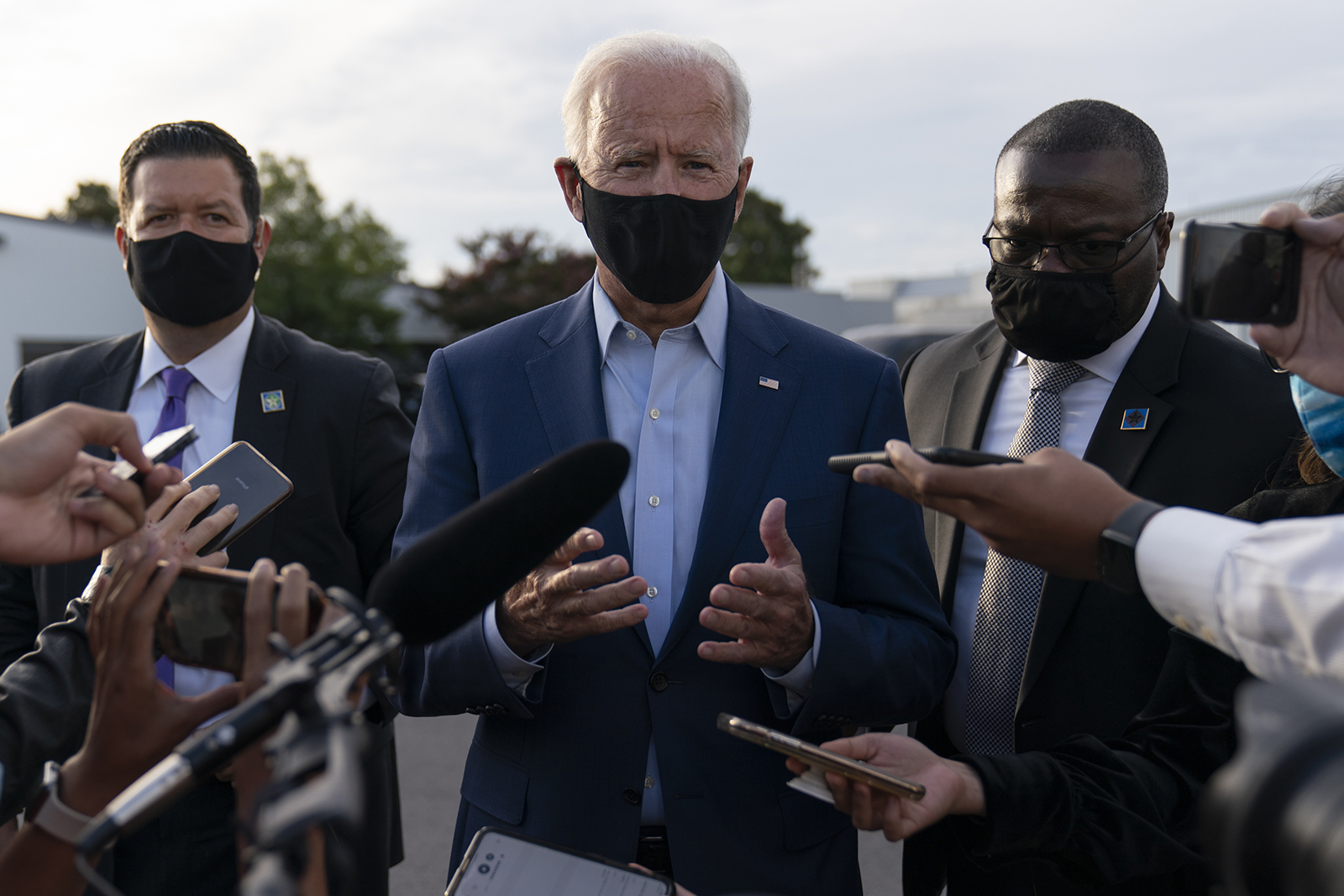 Democratic presidential nominee Joe Biden, flanked by members of his Secret Service detail, speaks to media about the Breonna Taylor ruling and other topics before boards a plane at Charlotte Douglas International Airport in Charlotte, North Carolina on Wednesday.