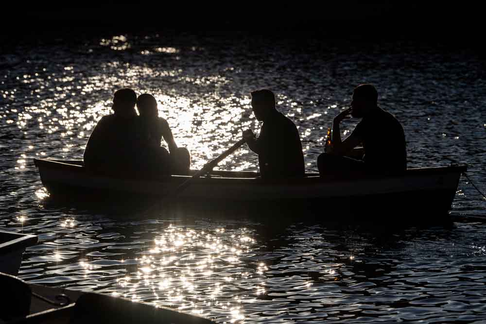Friends row a boat at Hollow Ponds in East London on May 31 in London, England, after the UK Government eased some coronavirus lockdown restrictions.