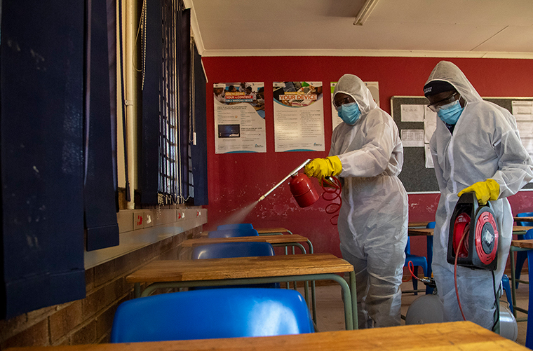 A disinfection team disinfects the classroom at Ivory Park Secondary School in Johannesburg, South Africa, Thursday, May 28, 2020, ahead of the June 1, 2020, re-opening of Grade 7 and 12 learners to school.