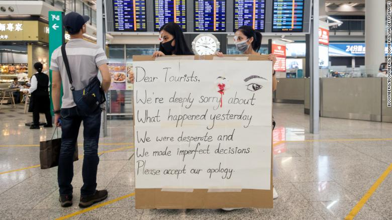 Protesters returned to the airport on Wednesday holding signs apologizing for the violence on Tuesday night.