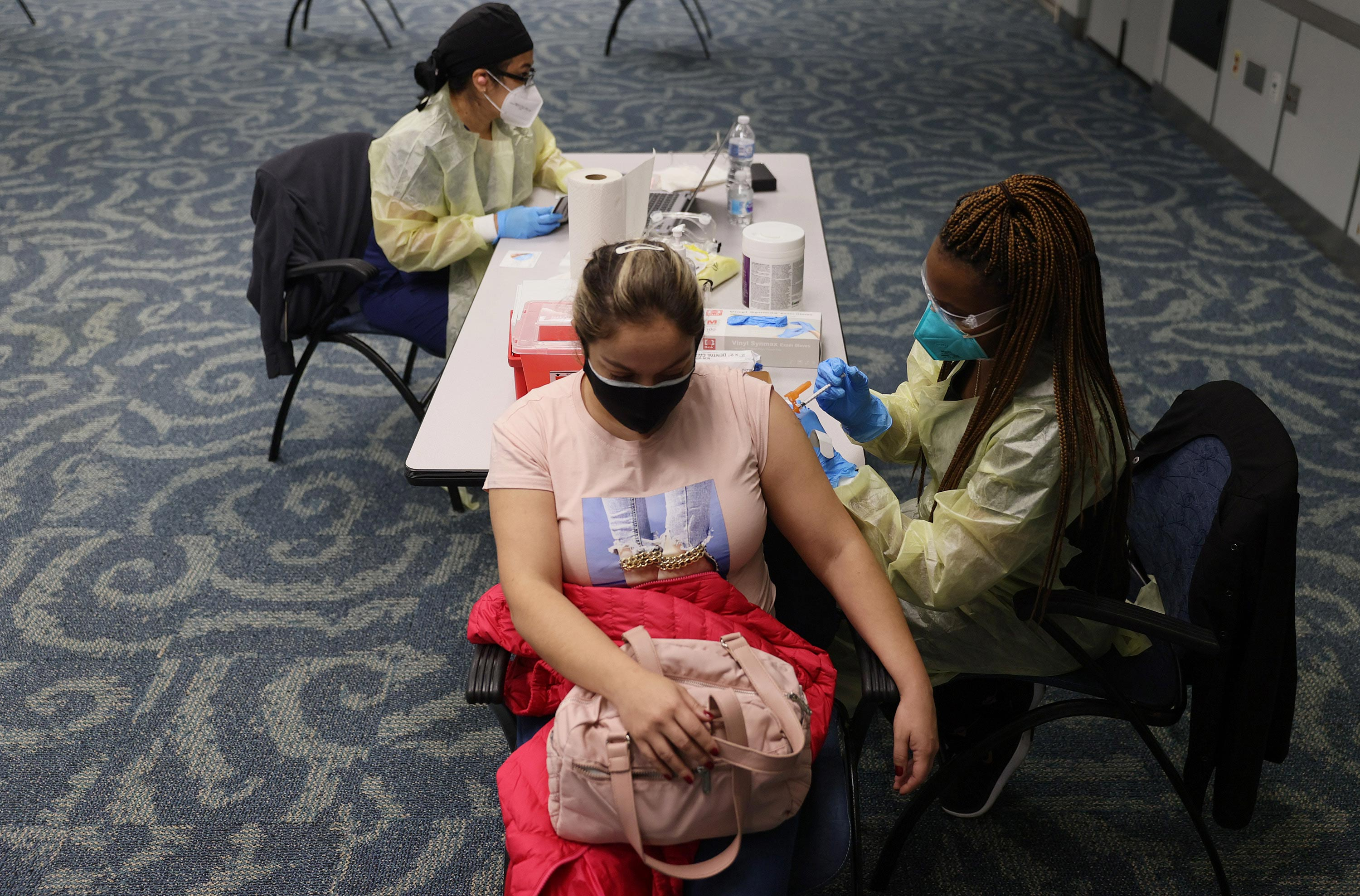 Lorena Castilla gets a Pfizer-BioNtech COVID-19 vaccination from a healthcare worker at Miami International Airport on May 10 in Miami.