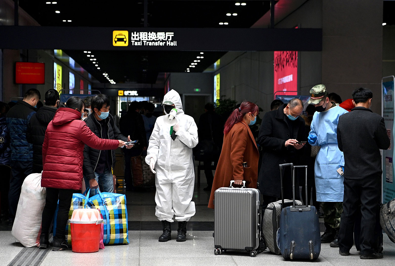 Passengers wearing face masks have their travel history checked as they arrive at the railway station in Hefei, China on March 4.