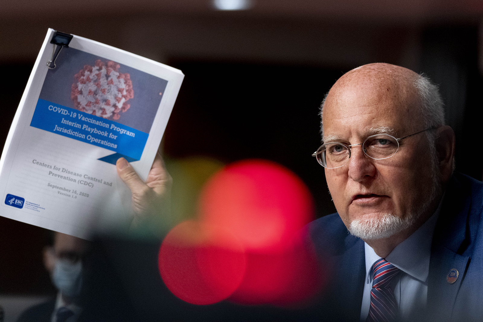 Director Dr. Robert Redfield holds up a CDC document while he speaks at a hearing of the Senate Appropriations subcommittee reviewing coronavirus response efforts on Wednesday in Washington.