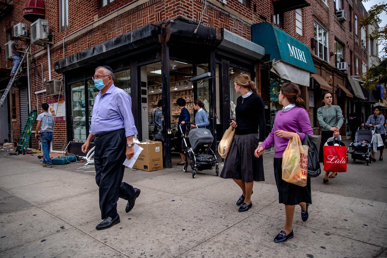People walk in the Borough Park neighborhood of Brooklyn, New York, on September 24.