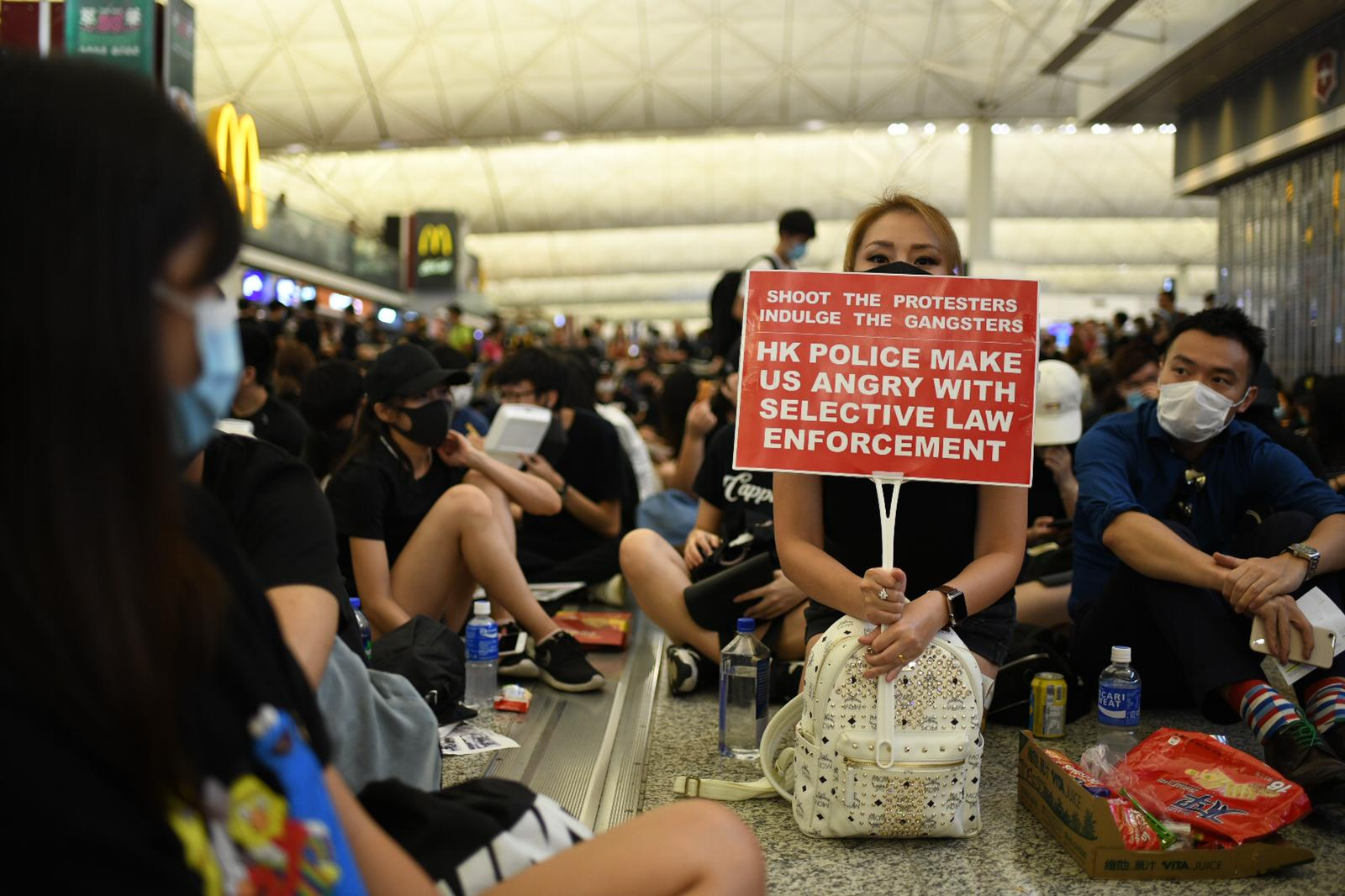 Demonstrators hold protest signs in the arrivals hall of Hong Kong airport.