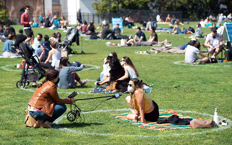 A woman is interviewed from inside a painted circle on the grass encouraging social distancing at Dolores Park in San Francisco, California on May 22, amid the novel coronavirus pandemic.