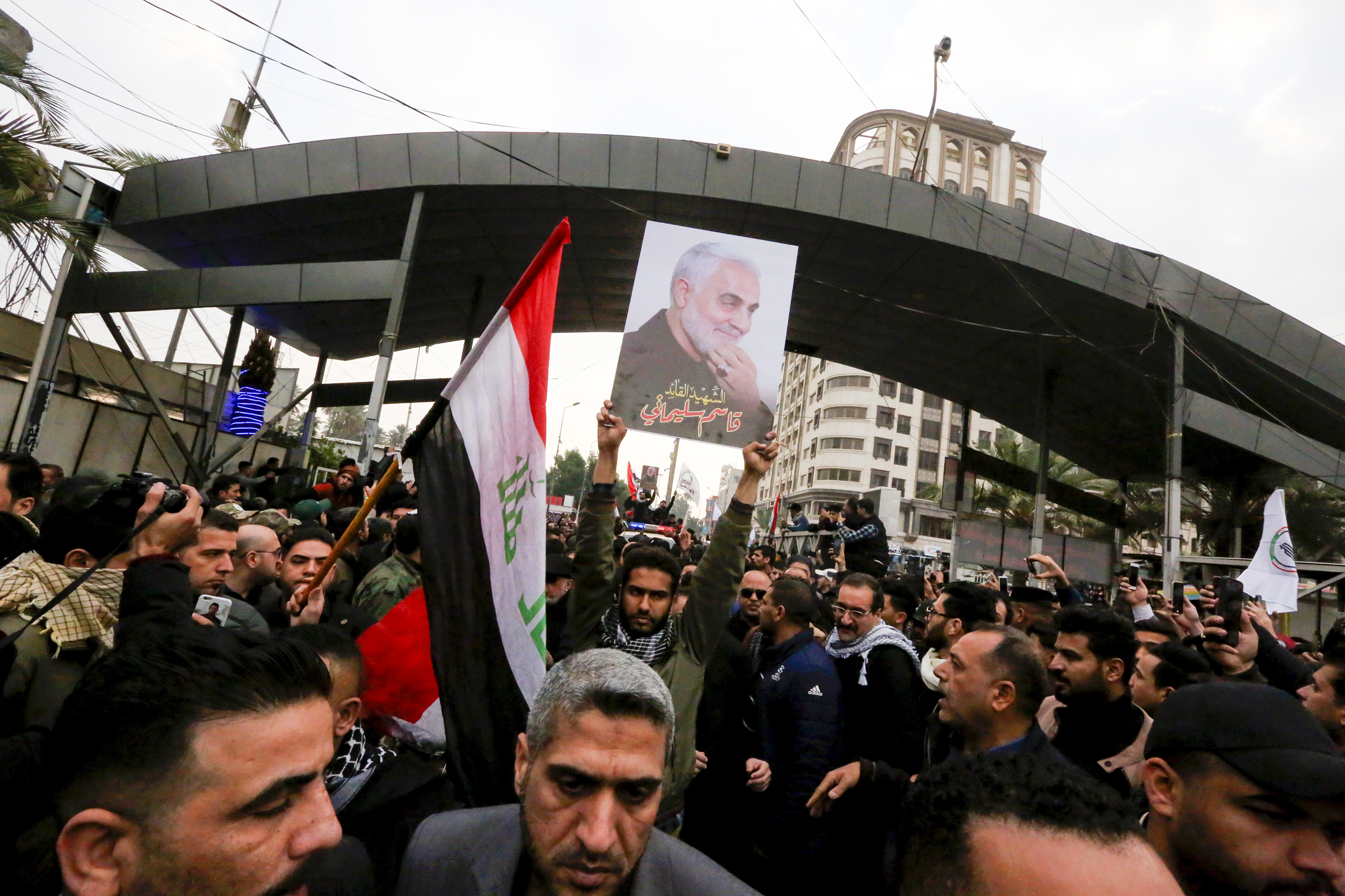 Mourners carry flags and the portrait Iranian military commander Qasem Soleimani.