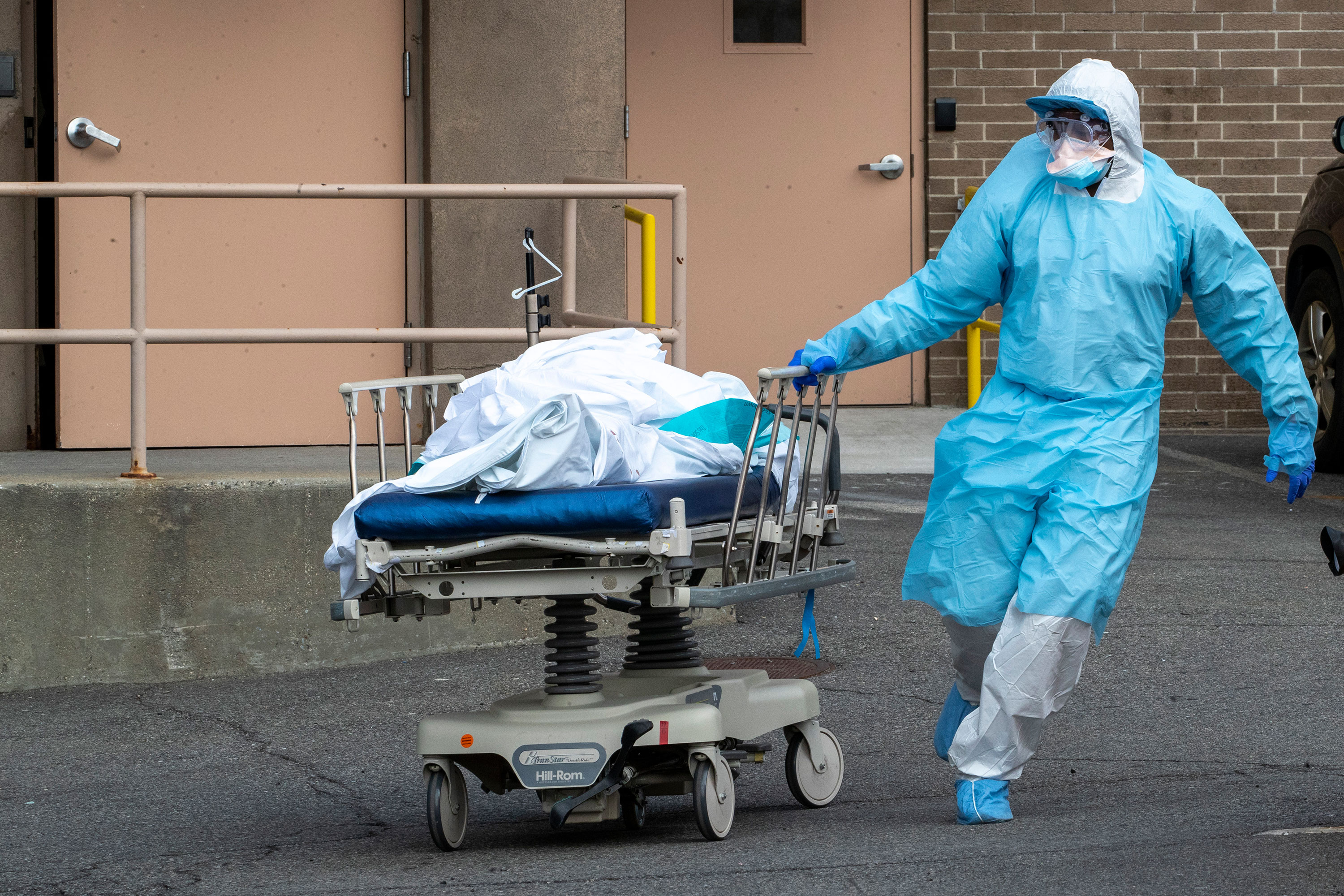 Medical personnel remove a body from theWyckoff Heights Medical Center to refrigerated containers parked outside, on April 2 in Brooklyn, New York.