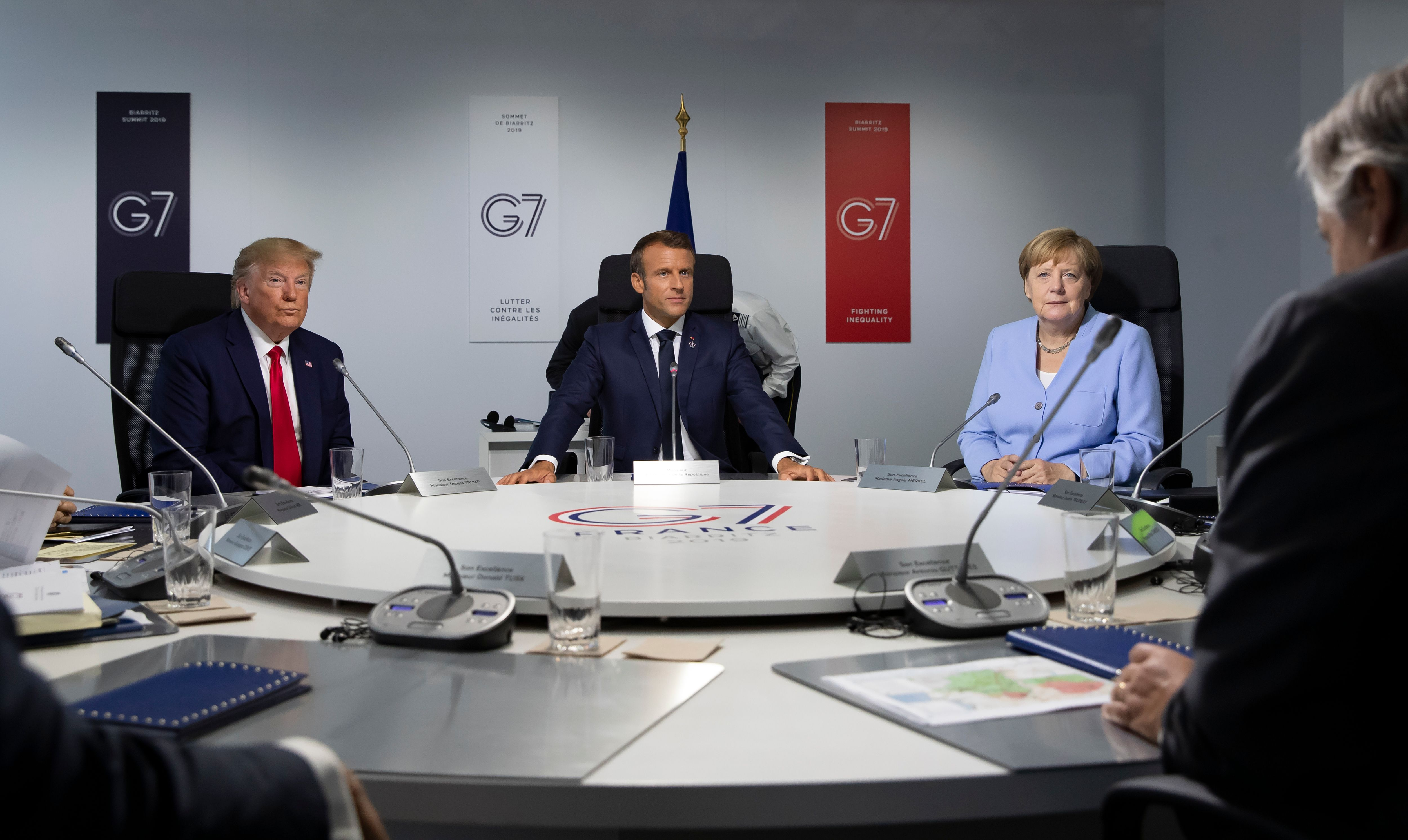 President Trump, French President Emmanuel Macron and Germany's Chancellor Angela Merkel attend a work session at the G7 Summit.