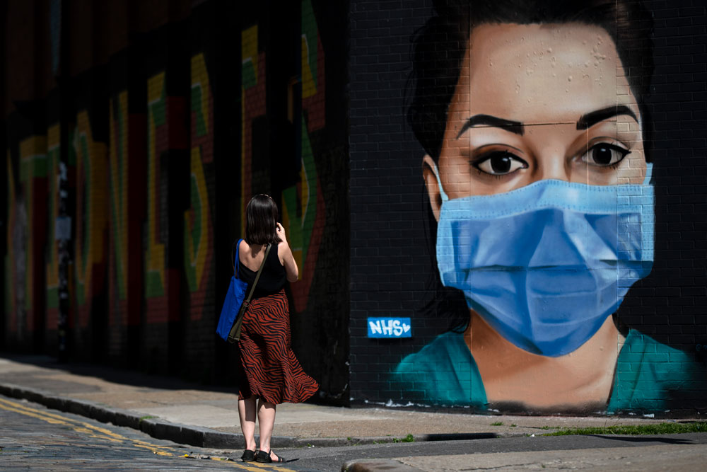A woman takes a photo of graffiti on Brick Lane in East London on April 23, in London.