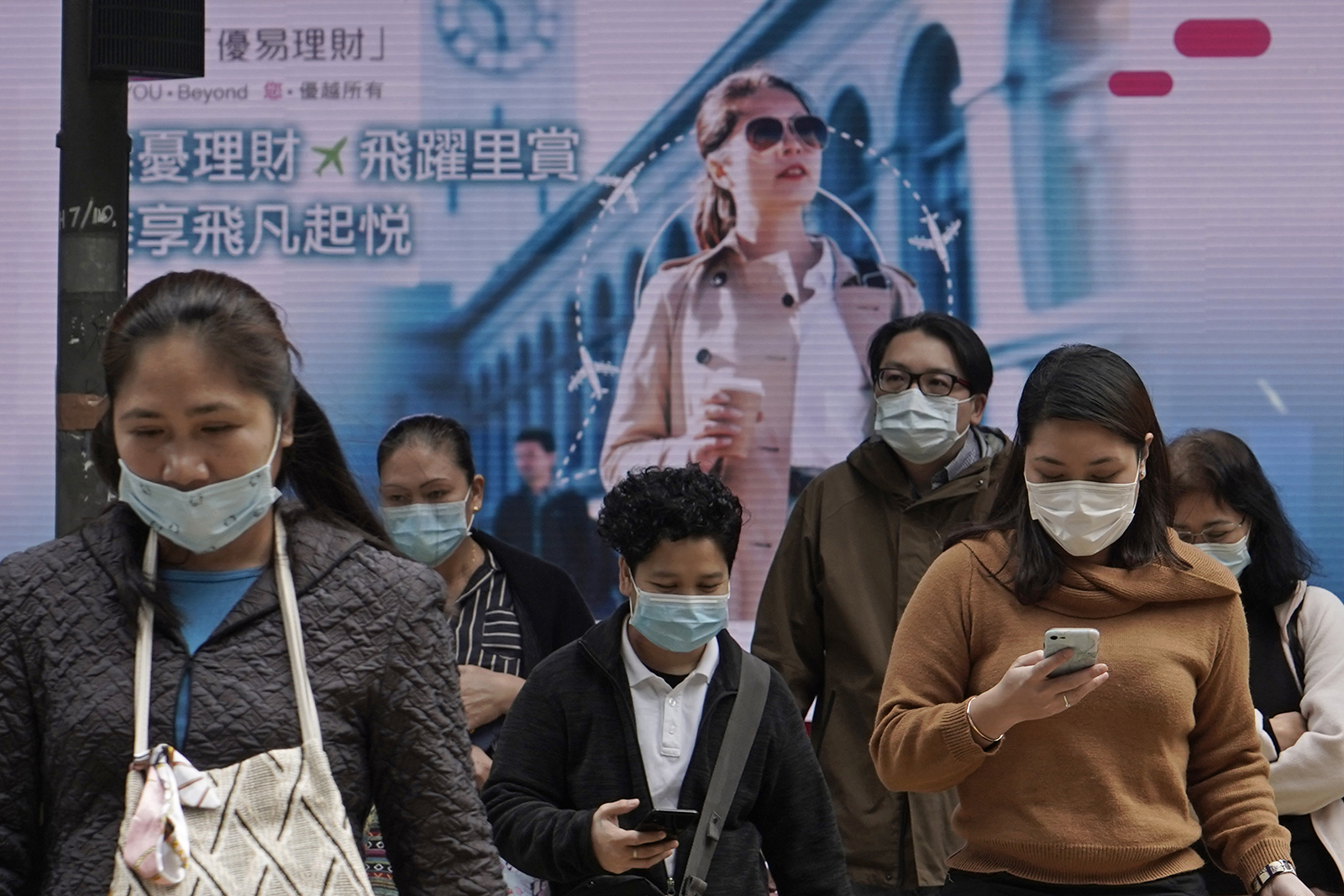 People wearing face masks walk on a street in Central, the business district of Hong Kong, on Tuesday, February 11.