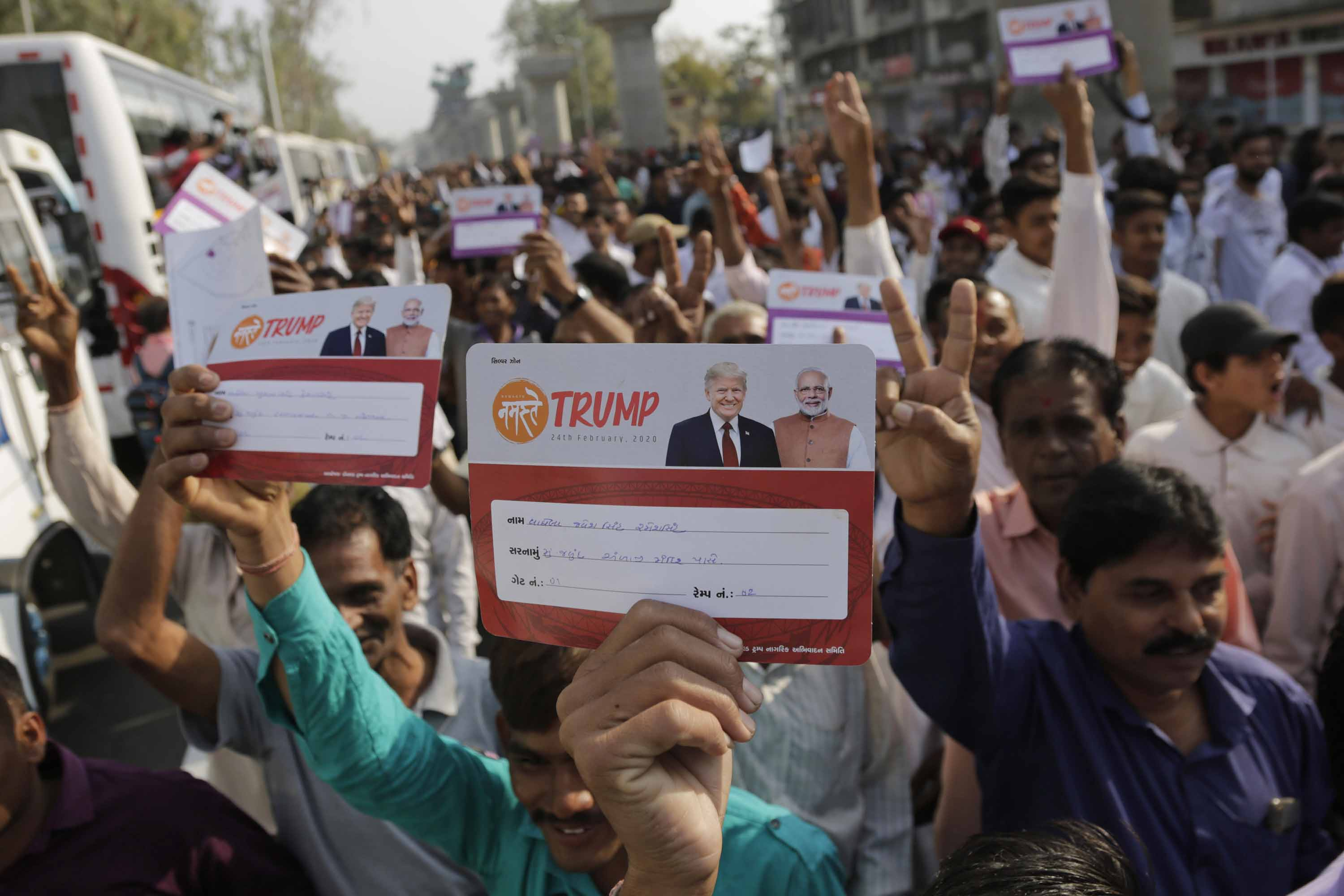 Indians display their passes as they arrive to attend the Namaste Trump event in Ahmedabad.