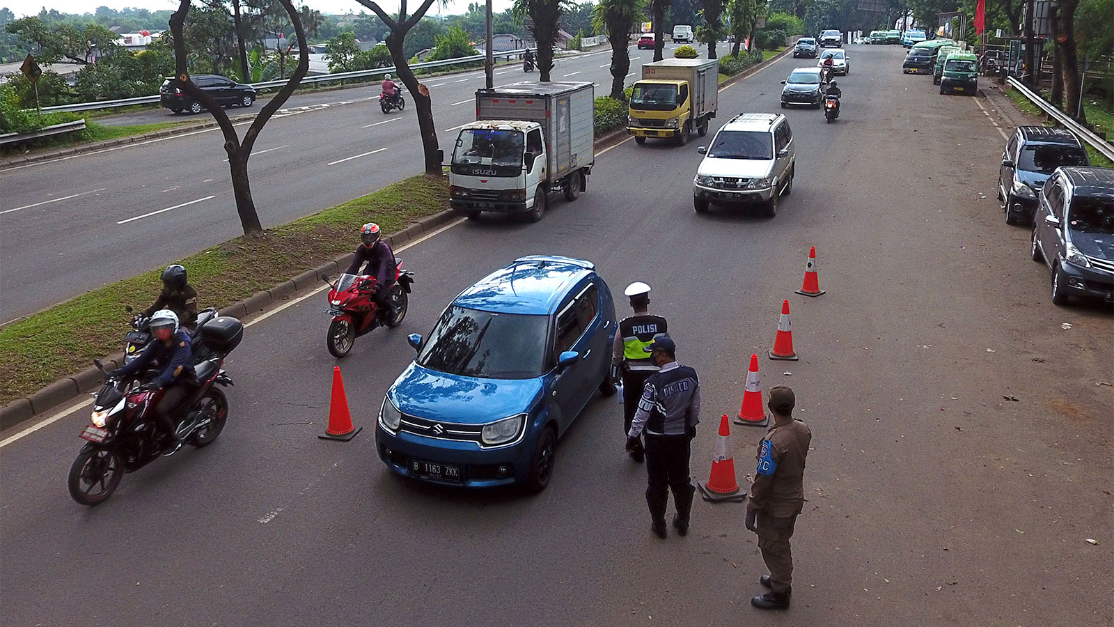Vehicles drive past a checkpoint during a partial lockdown in Serpong, West Java, Indonesia, on April 24.