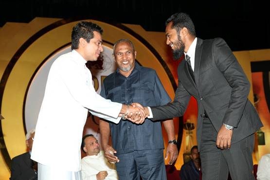 A photo posted in 2016 on the Sri Lankan Minister of Science Technology and Research's official Facebook page from a 2016 event shows Sujeewa Senasinghe (in white), former State Minister of International Trade, shaking the hand of Imsath Ahmed Ibrahim (right) as his father (middle), billionaire spice trader Mohamed Ibrahim, looks on.