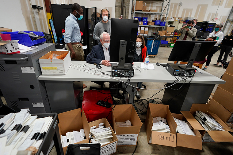 Democratic and Republican representatives review absentee ballots at the Fulton County Election preparation Center Wednesday, November 4, in Atlanta.