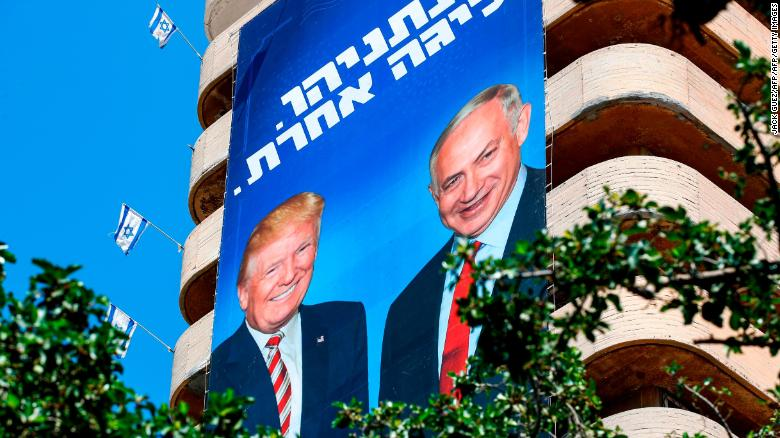 "A giant Israeli Likud Party election banner hangs from a building in Tel Aviv showing Netanyahu shaking hands with Trump, with a caption above reading in Hebrew ""Netanyahu, in a league of his own."""