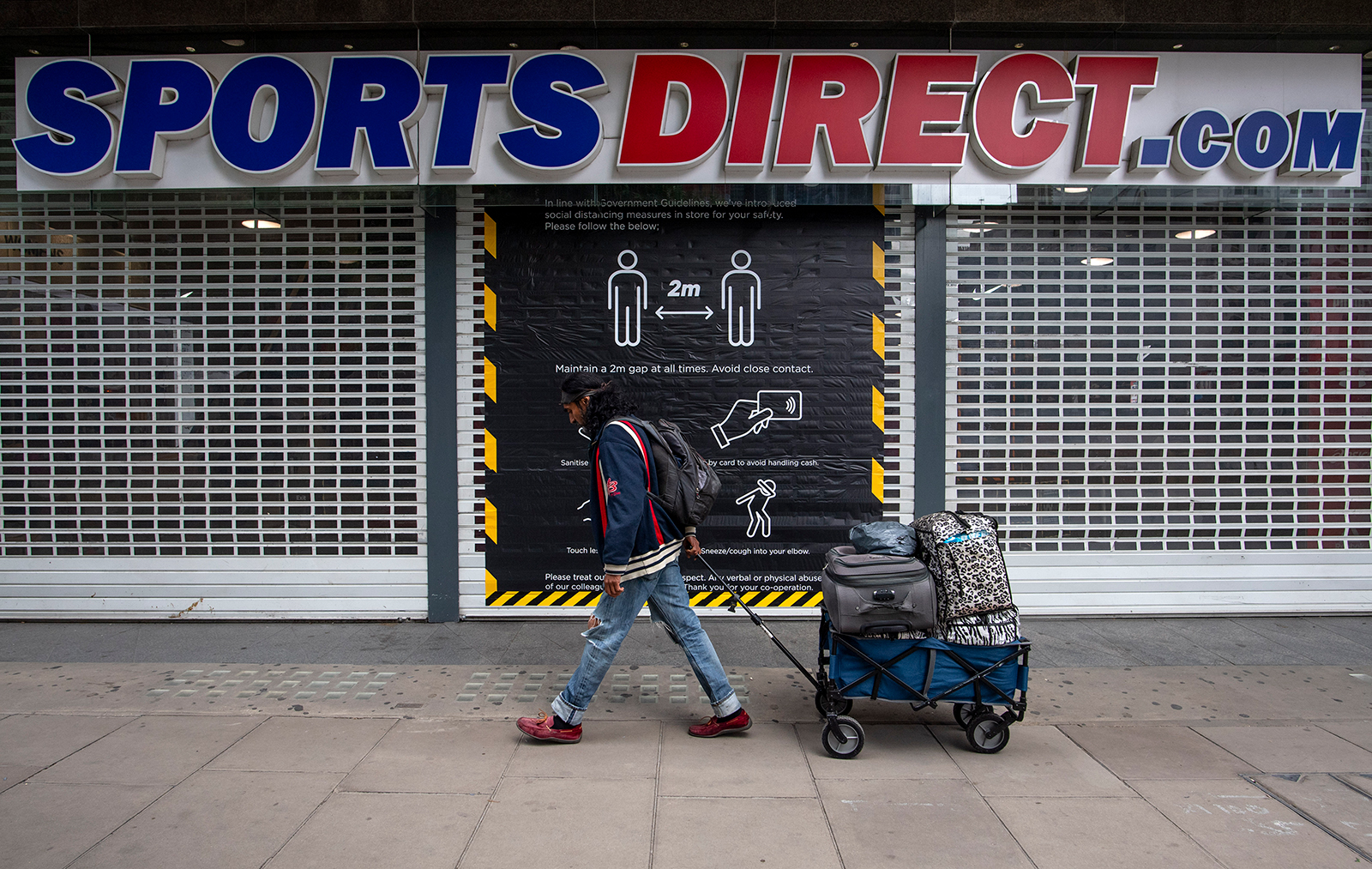 A man pulls luggage past a social distancing sign on the door of Sports Direct on Oxford Street on June 12, in London.