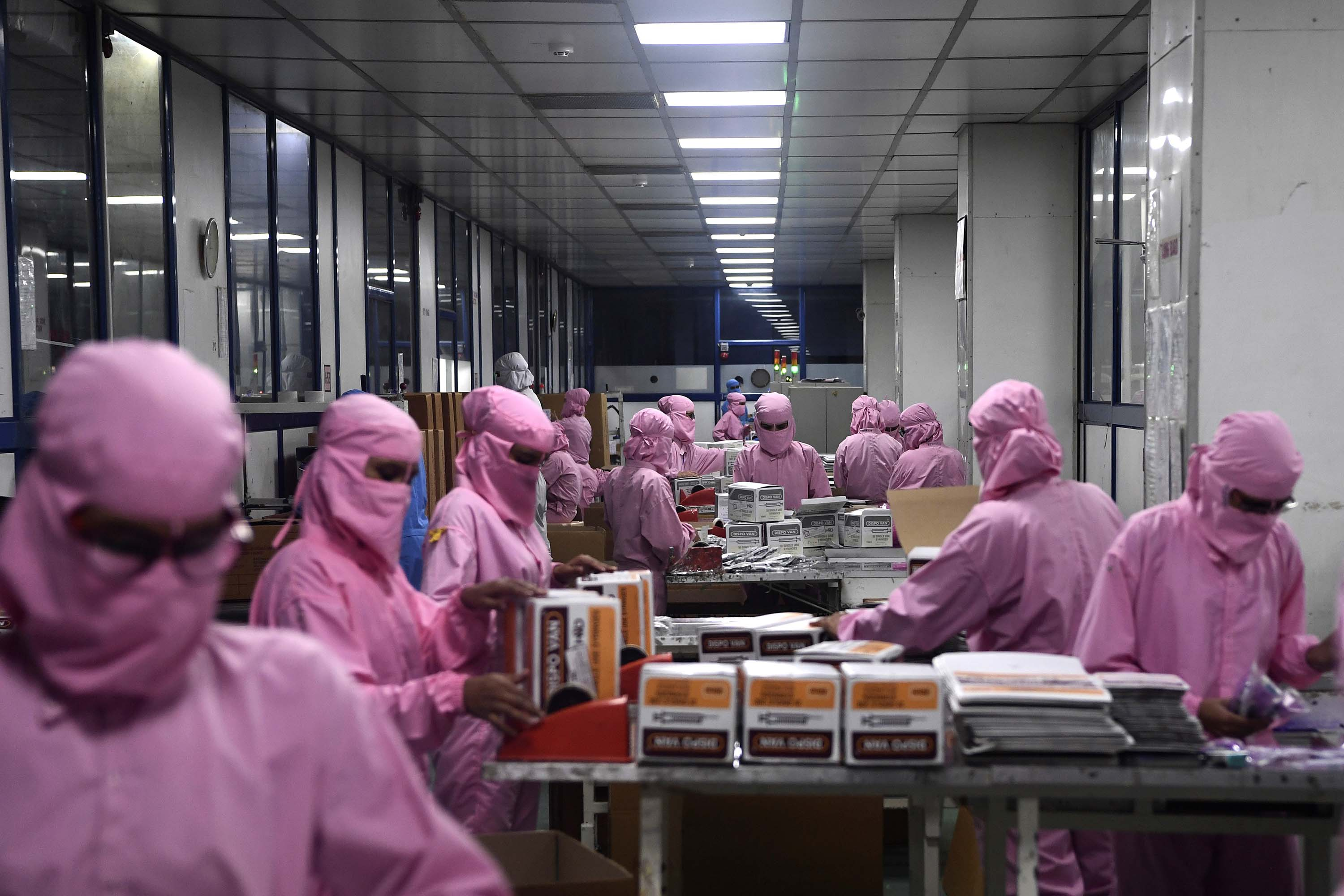 Workers pack syringes at the Hindustan Syringes factory in Faridabad, India. The manufacturer is ramping up its production, anticipating a surge in demand amid the global race to find a COVID-19 coronavirus vaccine.