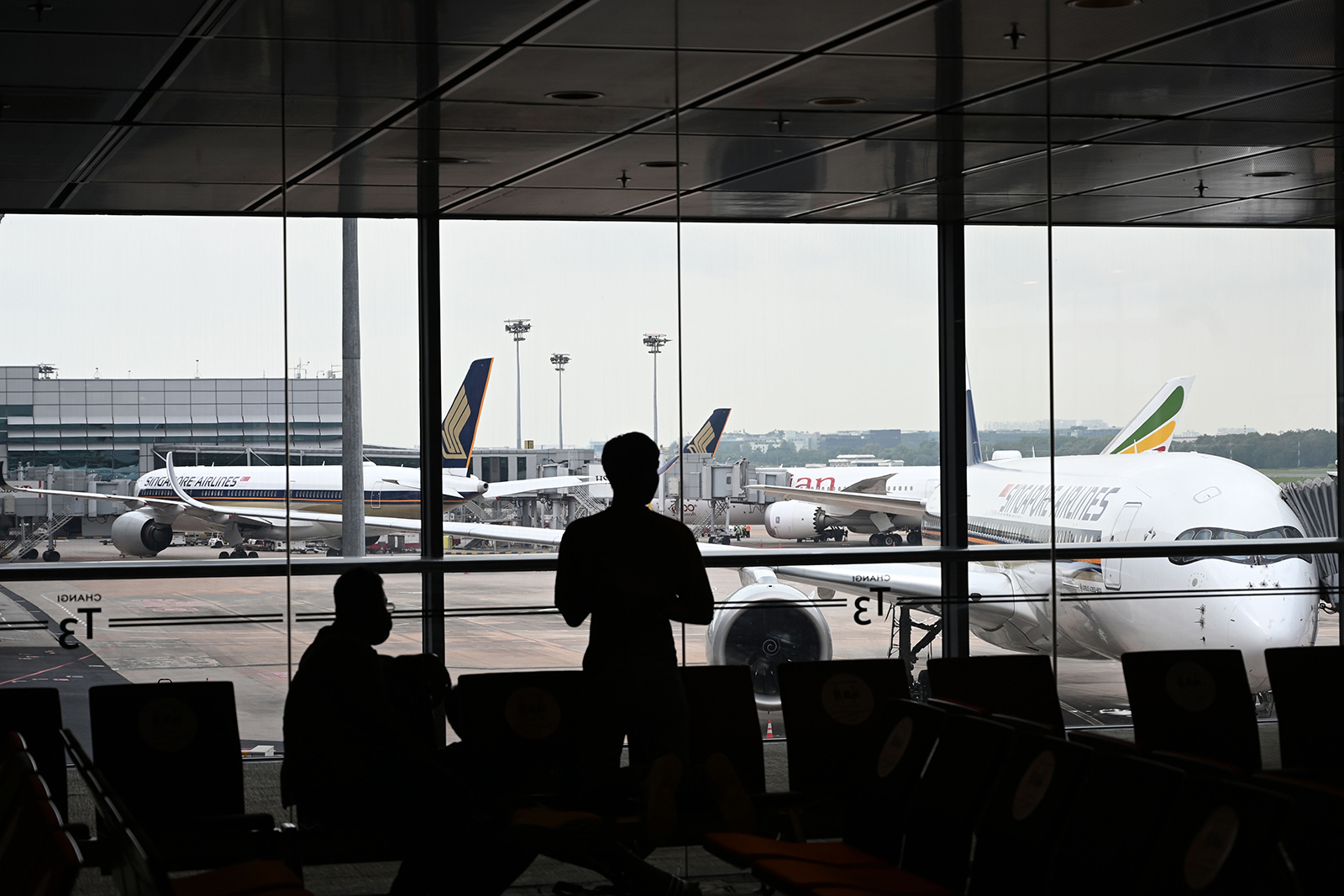 People are silhouetted against Singapore Airlines Airbus planes at Changi International Airport in Singapore on October 24.