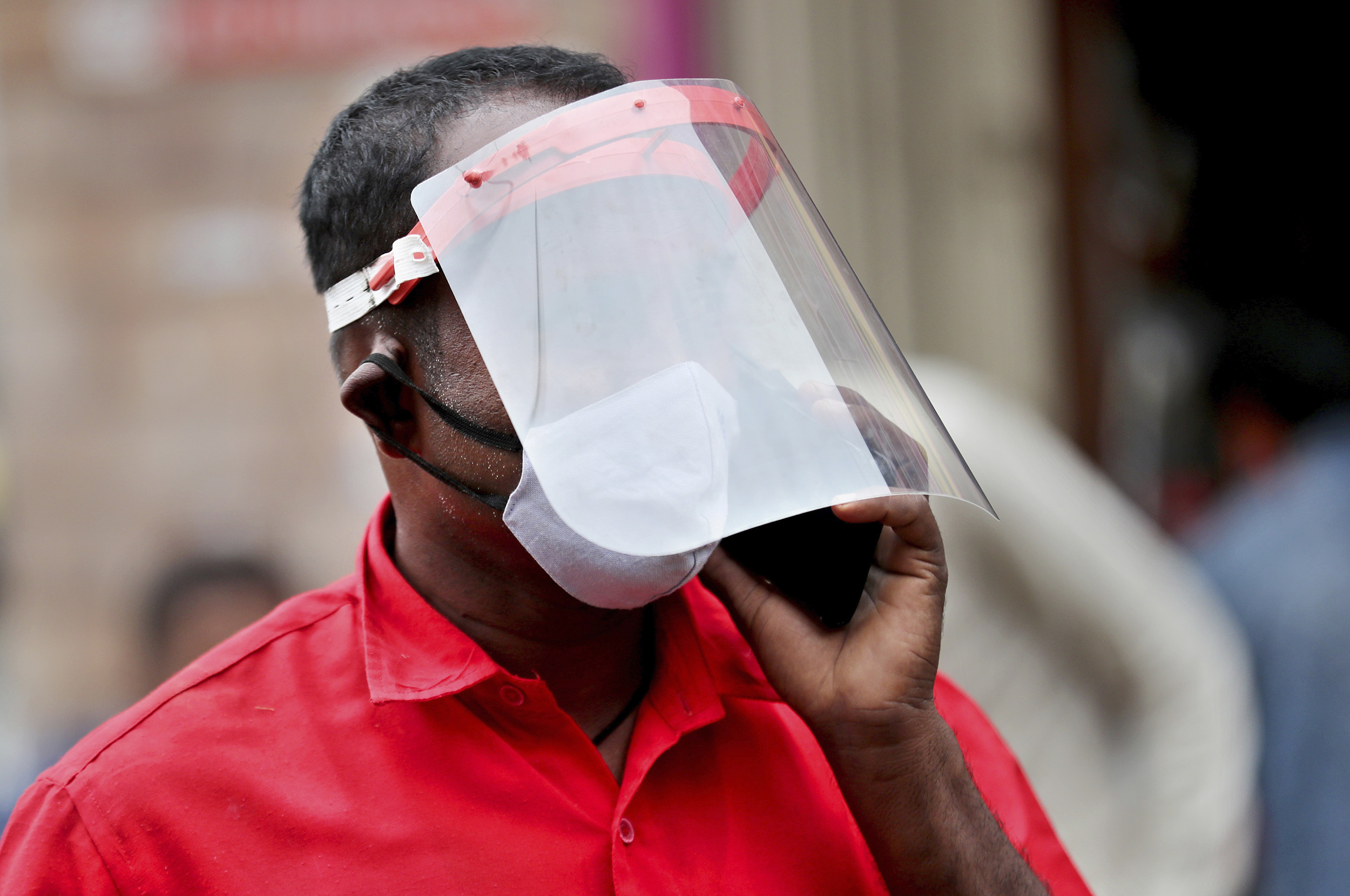 An Indian trader wears a face shield and mask as he talks on his mobile phone at a wholesale fruit market in Bengaluru, India, Saturday, May 30.