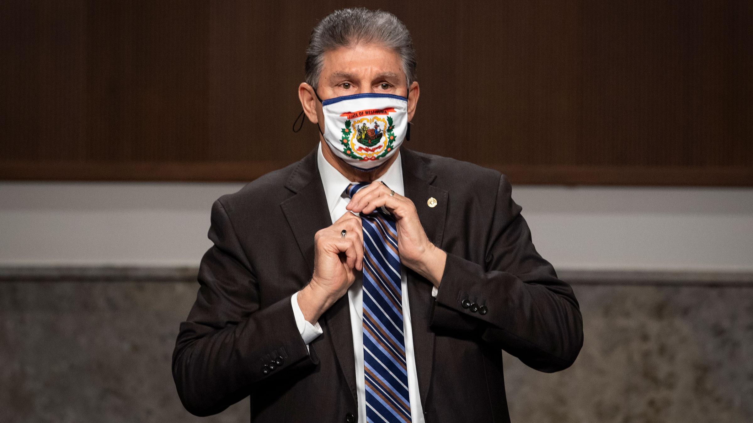 US Sen. Joe Manchin adjusts his tie during a meeting on Thursday.