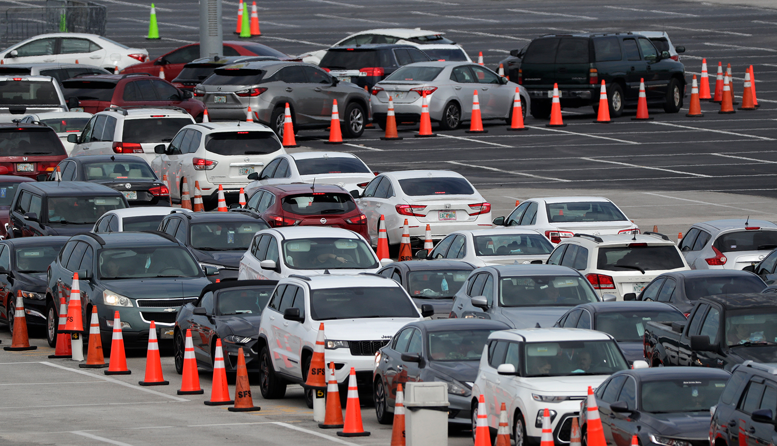 Lines of cars wait at a drive-through coronavirus testing site, on Sunday, July 5, outside Hard Rock Stadium in Miami Gardens, Florida.