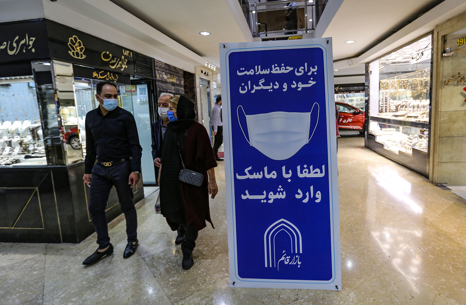 Iranians walk next to a sign advising people to wear masks on their way to shop in Tajrish square in the capital Tehran on November 1.