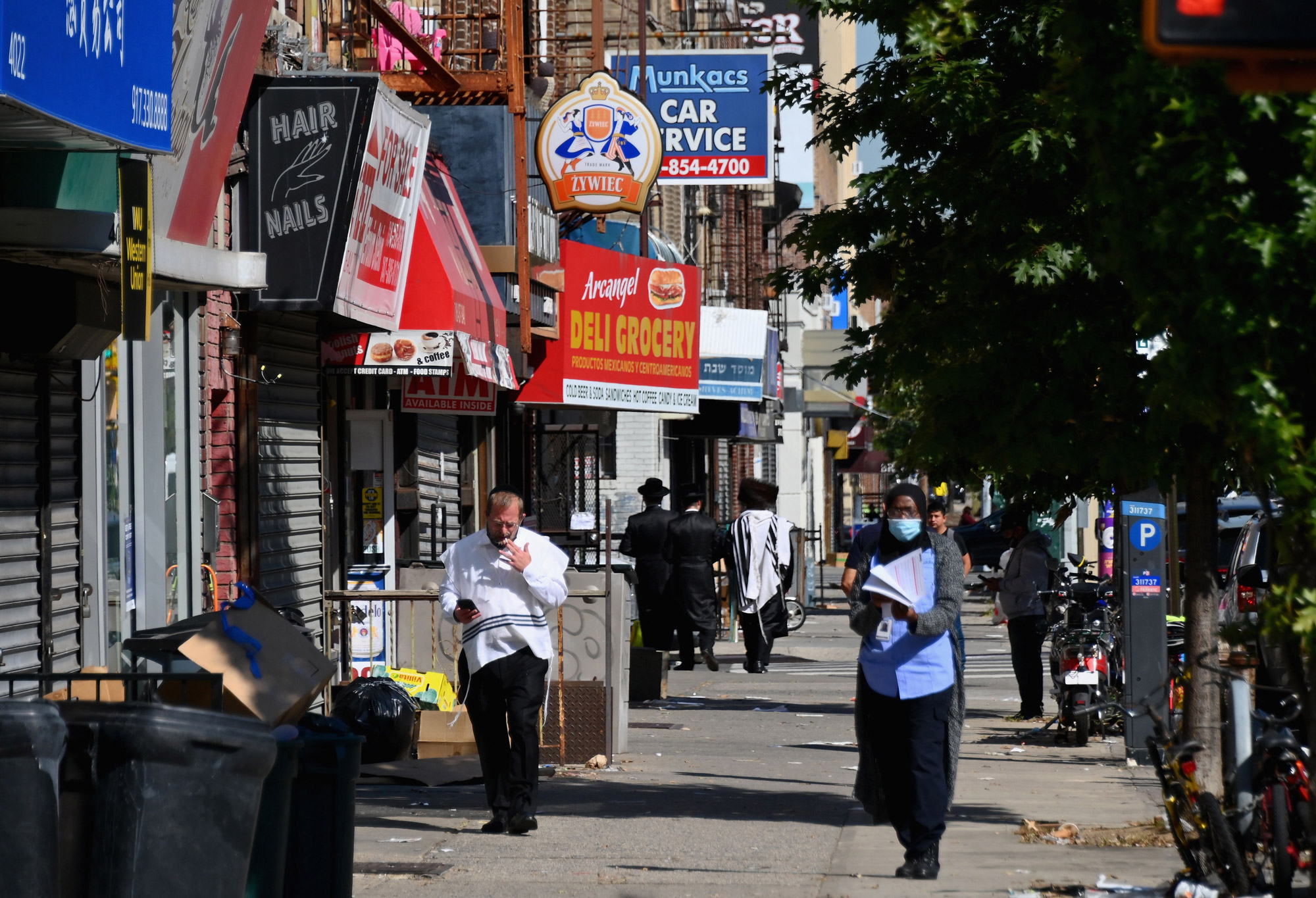 People walk past closed stores in the Borough Park section of Brooklyn, New York City, on October 9.