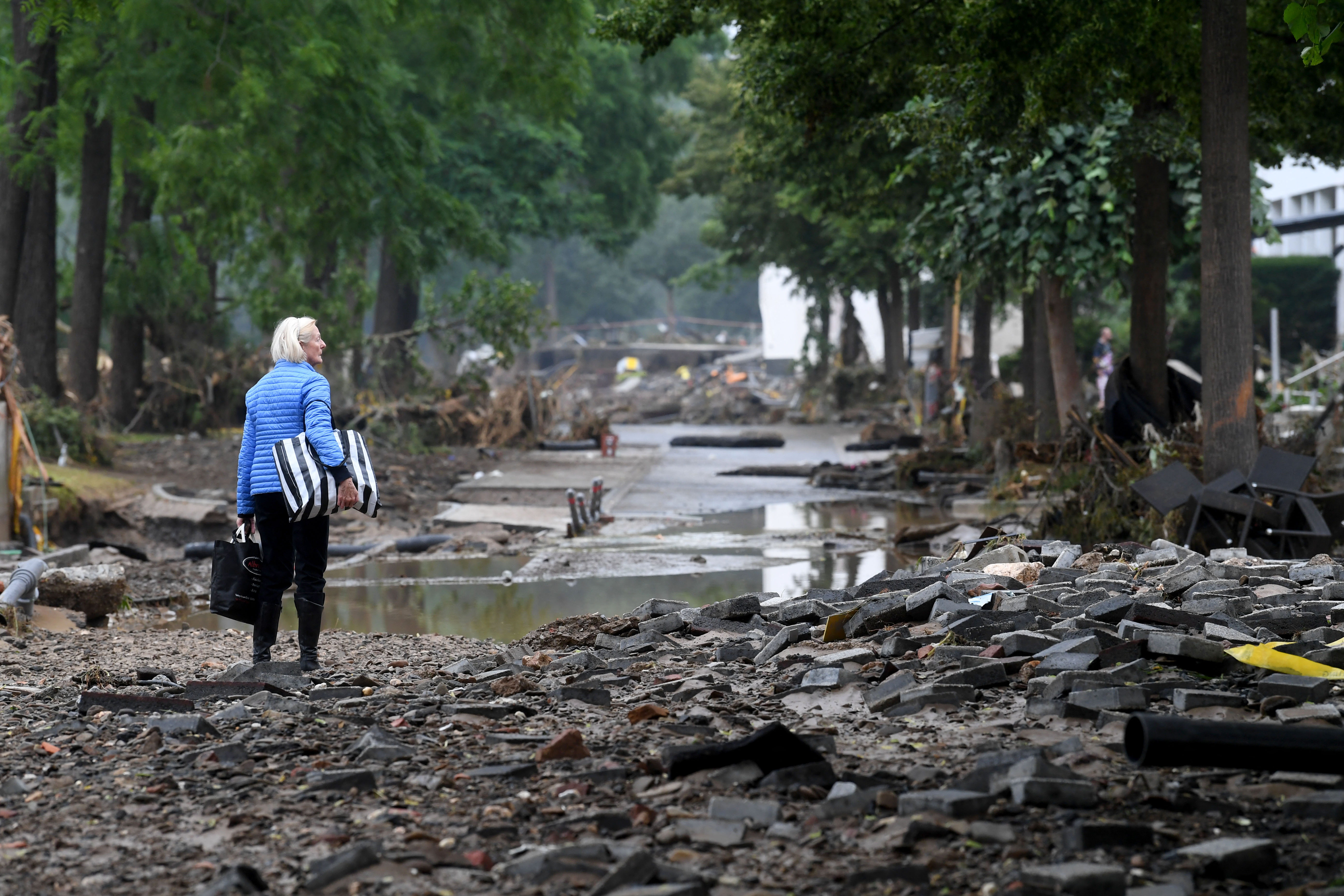 A woman carries bags in a devastated street after the floods caused major damage in Bad Neuenahr-Ahrweiler, western Germany, on July 16.