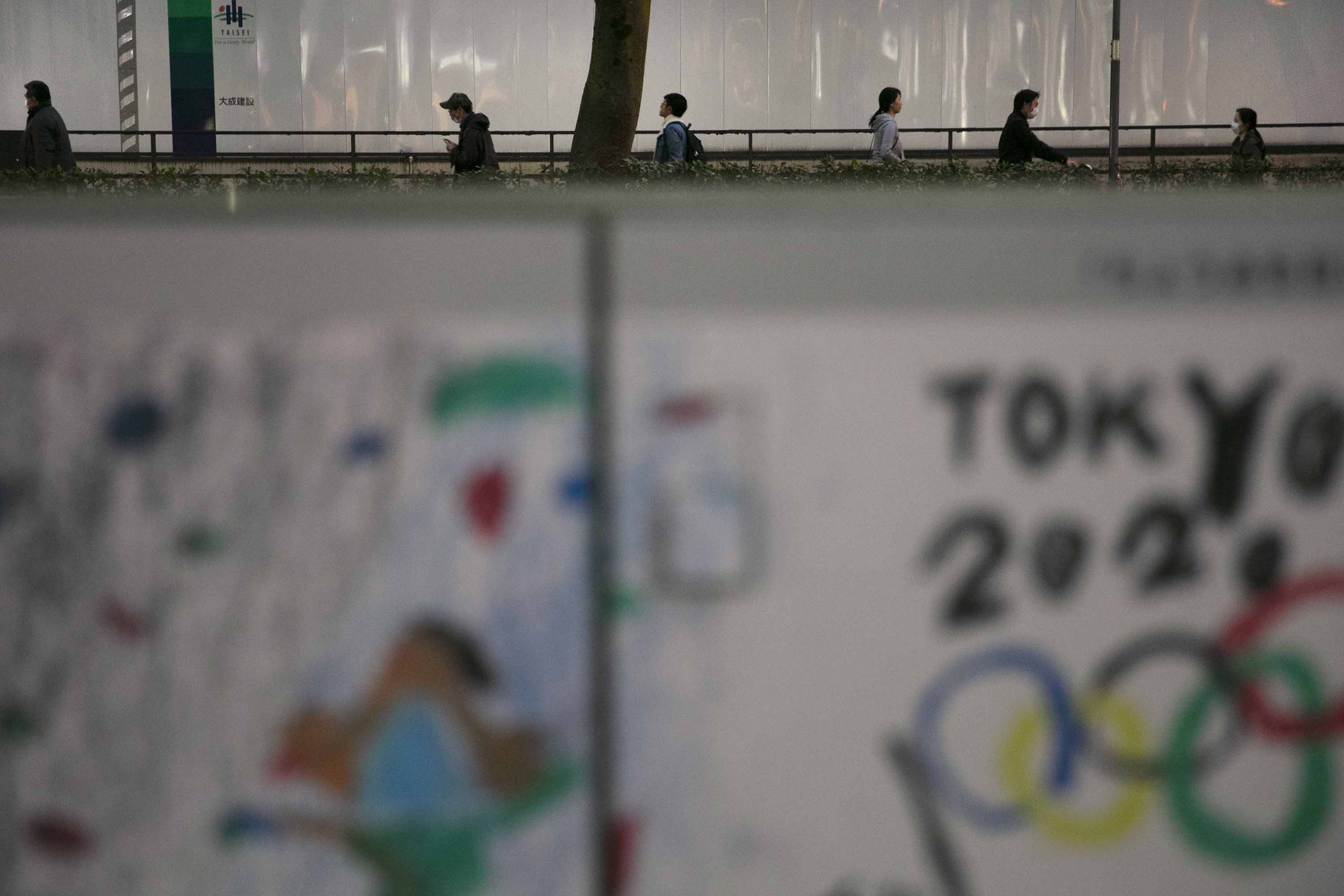 Commuters in Tokyo make their way past a poster celebrating the Tokyo 2020 Olympics, foreground, on Tuesday.